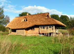 a house made of straw bales and a roof made of reed thatch for holiday rental by lake Hancza in Poland