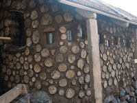 a cordwood porch with glass jars as windows and clay mortar