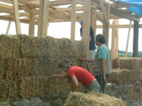 The straw bale wall being stacked.
