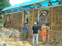 volunteers fixing the straw bale wall in Poland, Przelomka by lake Hancza