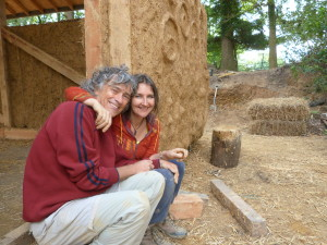 Paulina and Antony sitting in front of a clay plastered wall