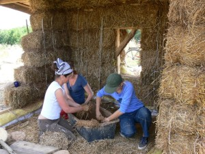 mixing the 1st coat of earthen plaster on a straw bale workshop